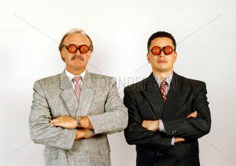 zwei Geschaeftsleute mit Tomaten auf Augen  ernst