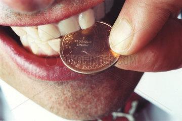 Mann beisst in Dollarmuenze um Echteheit zu pruefen