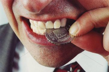 Mann beisst in schweizer Franken um Echteheit zu pruefen