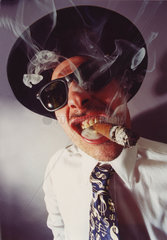 Kniffliger Mann raucht Zigarre