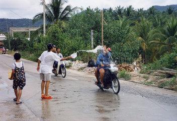 Thailand  Koh Samui  Songkran  Motorradfahrer wird nassgespritzt