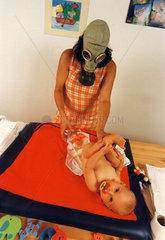 Frau mit Gasmaske wickelt Baby