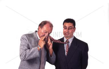 Geschaeftsmann schnaubt Anderem in die Krawatte