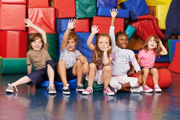 Kinder heben Haende in der Turnhalle