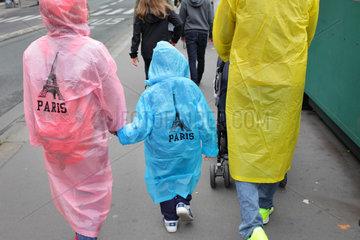 Paris  Frankreich  Familie mit Regenumhaengen und dem Aufdruck Paris