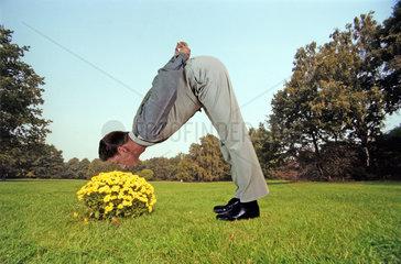 Mann riecht an gelben Blumen