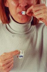 Frau trinkt aus winziger Teekanne und Tasse