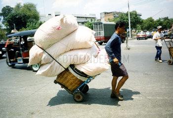 Mann zieht Wagen mit Kissen