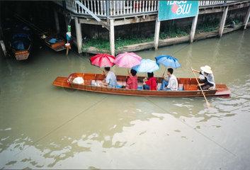 Vier mit Regenschirmen im Boot  Thailand