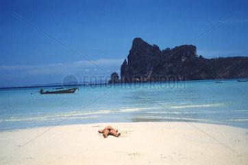 einsamer Strand  Mann sonnt sich