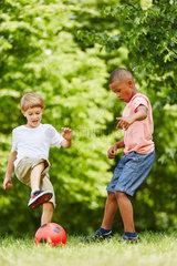 Freunde spielen Fussball im Park