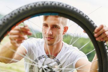 Junger Mann repariert Reifen