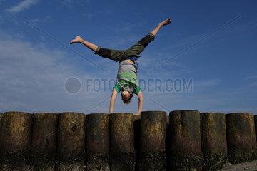 Wustrow  Deutschland  Junge macht einen Handstand auf einer Buhne