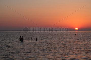 Strukkamp  Deutschland  Urlauber nehmen ein Bad bei Sonnenuntergang