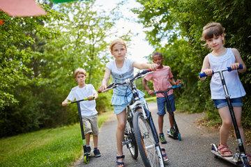 Gruppe Kinder faehrt mit Roller und Fahrrad