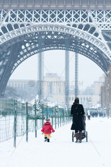 Woman and child walking by the Eiffel Tower