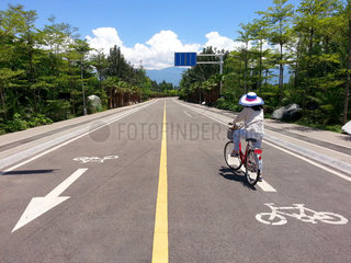 woman with a hat riding a bicycle on a track with mountains in t