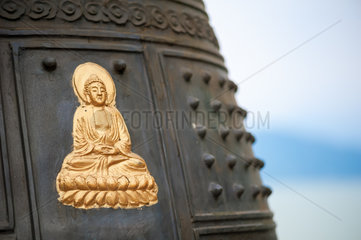 Golden colored Buddha on a ring bell in China