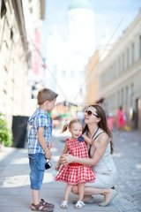 Young beautiful woman with her two kids in city at summer day