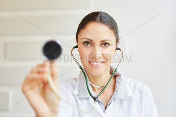 Aerztin haelt ein Stethoskop