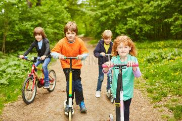 Gruppe Kinder mit Tretroller und Fahrrad