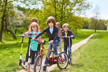 Kinder mit Fahrrad und Roller auf einem Ausflug