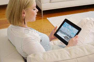 Hamburg  Deutschland  eine junge Frau sieht sich Fotos auf dem IPad von Apple an -Programm