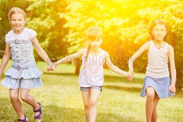 Gruppe Maedchen laufen zusammen im Sommer