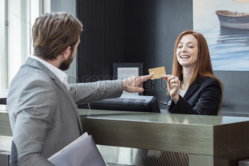 Businessman giving credit card to female receptionist