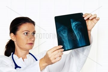 Young doctor in her doctor's office with an x-ray