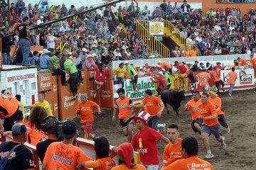 San Jose  Costa Rica  Maenner laufen in einer Arena vor einem Kampfstier davon