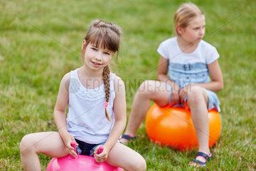 Freundinnen sitzen auf einem Huepfball