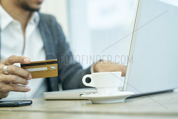 Mid section of businessman holding credit card