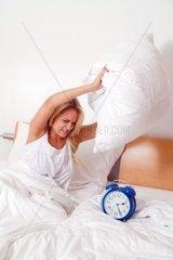 Junge Frau aergert sich beim Aufwachen und Aufstehen Wecker  Uhr laeutet