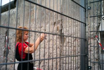 Berlin  Deutschland  Frau fotografiert Ueberreste der Berliner Mauer