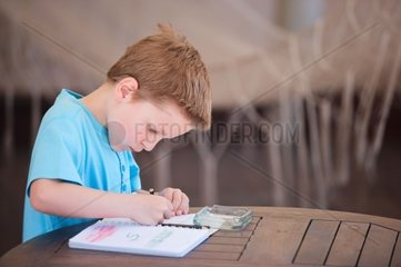 Little boy drawing or writing at outdoor terrace