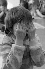 Berlin  DDR  ein kleiner Junge haelt sich die Augen zu