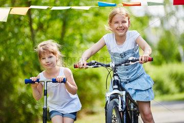 Maedchen fahren mit Roller und Fahrrad