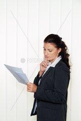 Unternehmerin liest einen Brief im Buero Nachricht vom Anwalt oder Finanzamt
