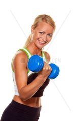 A young woman with dumbells at training for strength and fitness