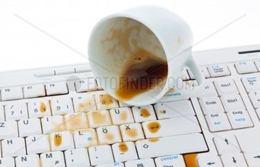 Kaffeetasse ausgeschuettet auf Tastatur eines Computers Schaden fuer Versicherung