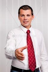 Geschaeftsmann bietet Handschlag zur Begruessung Im Buero