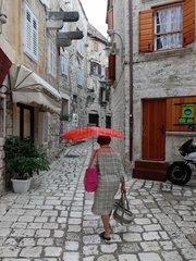 Hvar  Kroatien  Frau mit rotem Regenschirm geht durch die Gassen