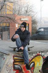 Bremen  Deutschland  Jugendlicher mit Skateboard am Rand einer Halfpipe