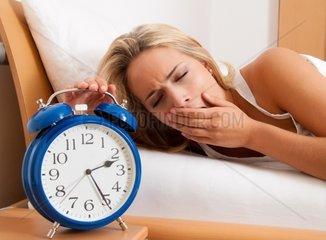 Schlaflosigkeit mit Uhr in der Nacht Frau kann nicht schlafen