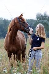 Brieselang  Deutschland  Maedchen schaut ihr Pferd liebevoll an
