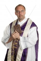 a Catholic priest with bible in worship