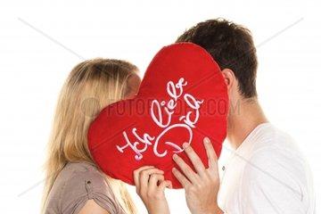 Loving couple kissing behind a heart Love is beautiful Secret love