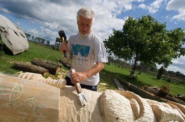 Wollin  Polen  ein Holzbildhauer arbeitet im Garten