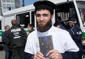 Berlin  Deutschland  Mann zeigt den Koran  im Hintergrund Polizei